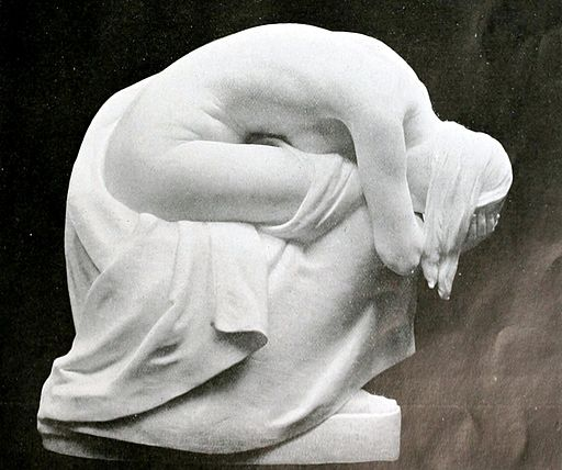 sculpted figure bent over in grief