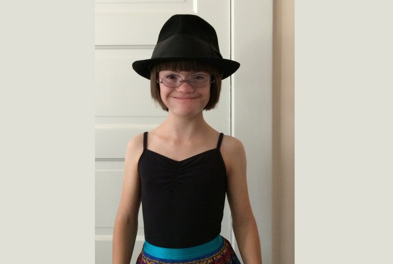 Young girl with Down syndrome wearing a big hat