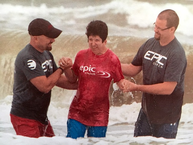 Woman emerges from the ocean waves assisted by two men
