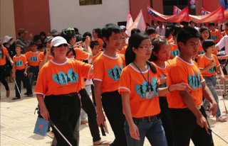 group of youth walking with matching shirts and white canes