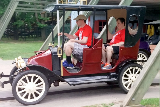 Two people in an antique car ride at amusement park