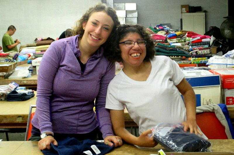 Two smiling young women sort materials in warehouse