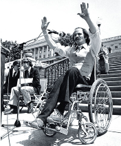 Black and white picture of Ron Kovic in his wheel chair at a protest