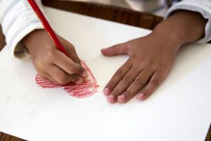 boy's hands coloring in a drawing of a heart
