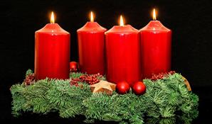 four lit red candles in green wreath on table