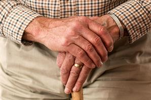image of elderly man's torso and his hands resting on a cane