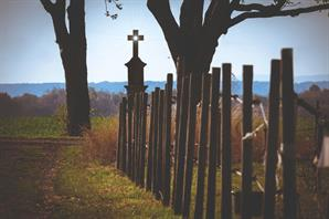 landscape of field with the sun shining through a hole in the center of a cross on the corner of an old picket fence