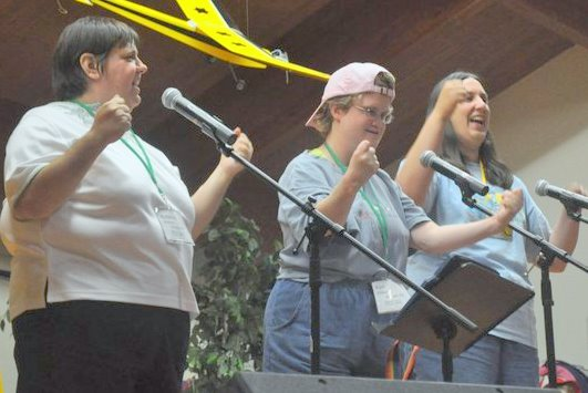 three women on stage gesture with their arms as they sing into microphones