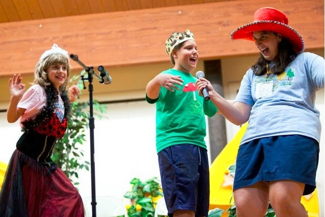 Two children and a woman wear silly hats on stage