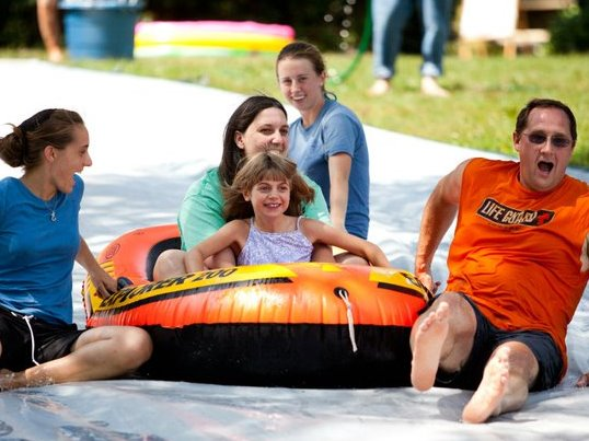 Two people in inflatable raft at the bottom of a waterslide, two others guide raft