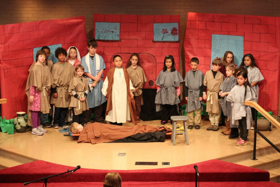 Children in biblical costumes line up on stage behind boy lying on pallet