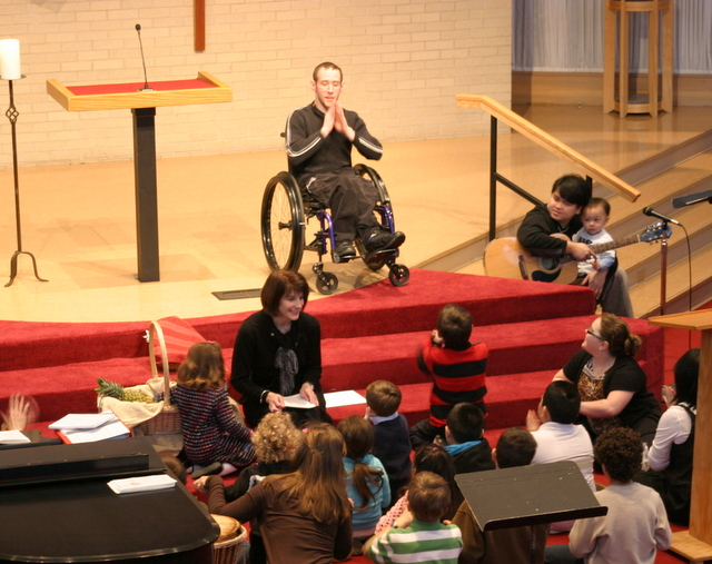 Man in wheelchair on stage is signing before children gathered on steps