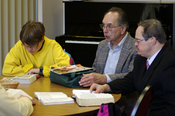 three people with open Bibles sit at a table