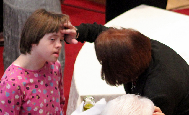 woman touches forehead of girl with Down syndrome