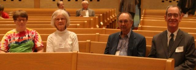 Four people sit side by side on church pew