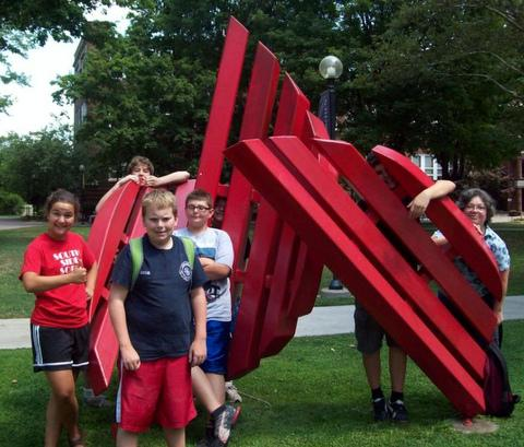 youth peer from behind large, red, abstract outdoor sculpture