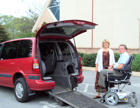 Man sits on power wheelchair next to standing woman and  red van with tailgate open and ramp down.