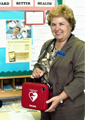 Carolyn Stoll stands in front of a bulletin board with a red first aid box