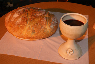 round loaf of bread beside chalice of wine