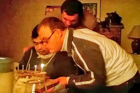 2 friends work together to blow out birthday candles