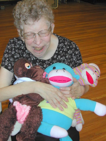 Woman sitting with stuffed animals.