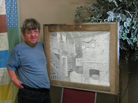 Gary stands next to the pencil drawing of a home's interior