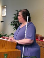 Woman with white cane stands at pulpit