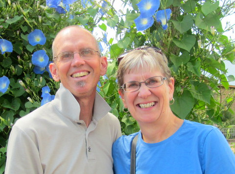 Mike and Mary Yoder in front of a mass of blue morning glories
