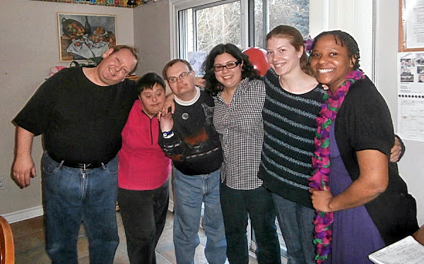 group of friends stand arm in arm, some with intellectual disabilities