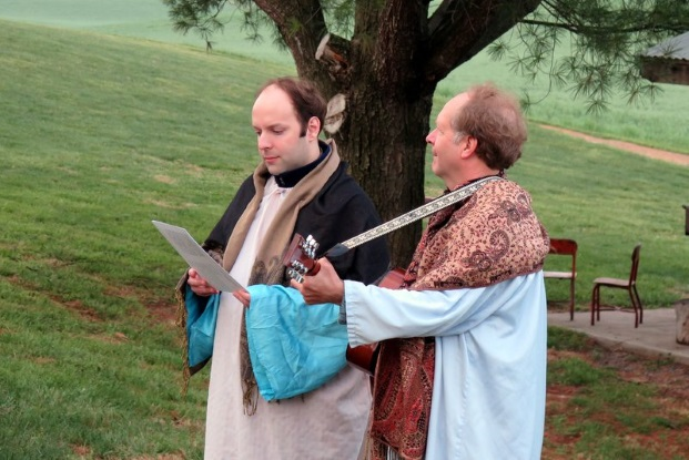 two men in biblical costumes sing with guitar outdoors