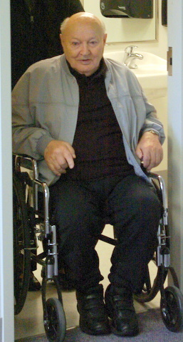 Man in wheelchair framed by doorway, with view of washroom sink behind him