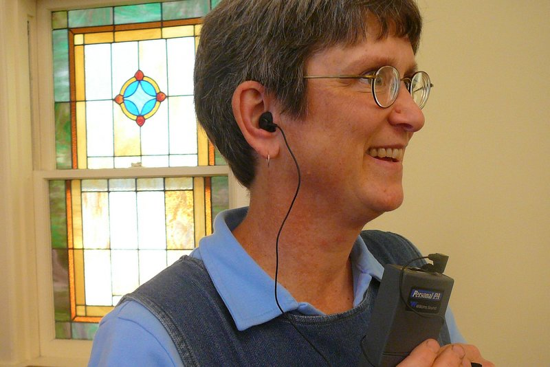 person wearing assistive listening device in a church
